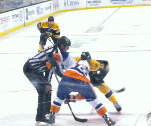 Bruins and Islander players square off and get ready for the puck to drop in a face-off.