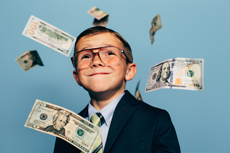 A+young+boy+accountant+wearing+glasses+and+suit+watches+U.S.+currency+while+more+falls+from+above.+He+is+smiling+and+ready+to+do+your+taxes+for+the+IRS+and+make+your+tax+refund+much+more+money.